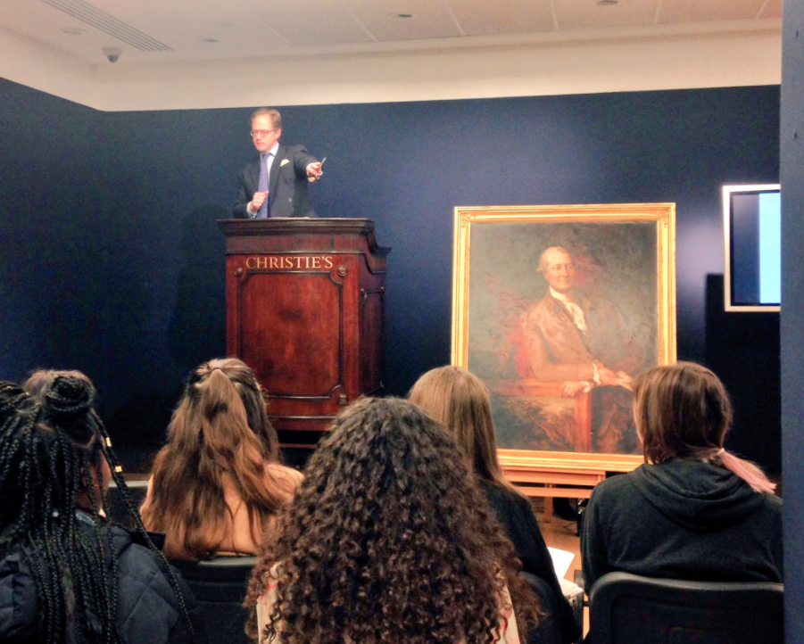 Students participate in a mock auction at Christie's Auction House